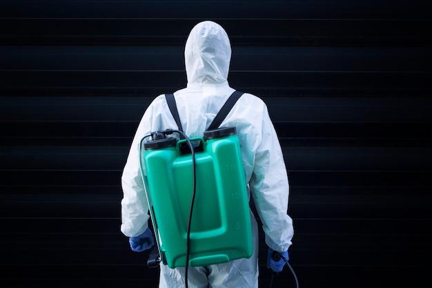 Homem em traje de proteção branco com reservatório para pulverização e desinfecção Foto gratuita