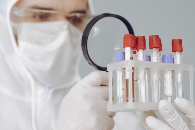 Homem em traje de proteção e óculos trabalhando no laboratório Foto gratuita
