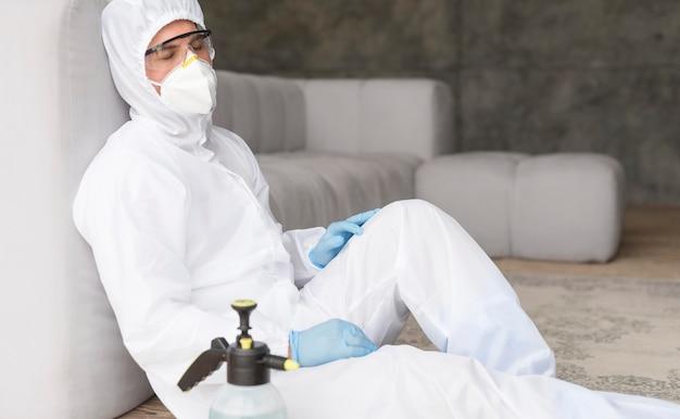 Homem em traje de proteção sentado Foto gratuita