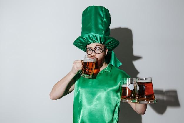 Homem em traje de st.patriks, bebendo cerveja e segurando copos Foto gratuita