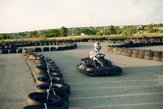 Homem em um circuito de kart com um carro Foto gratuita