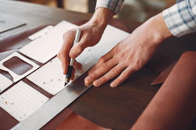 Homem em um estúdio cria artigos de couro Foto gratuita