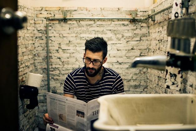 Homem, em, um, restroom, leitura, jornal Foto gratuita