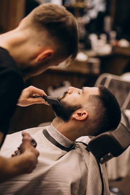 Homem em um salão de barbearia, fazendo o corte de cabelo e barba Foto gratuita