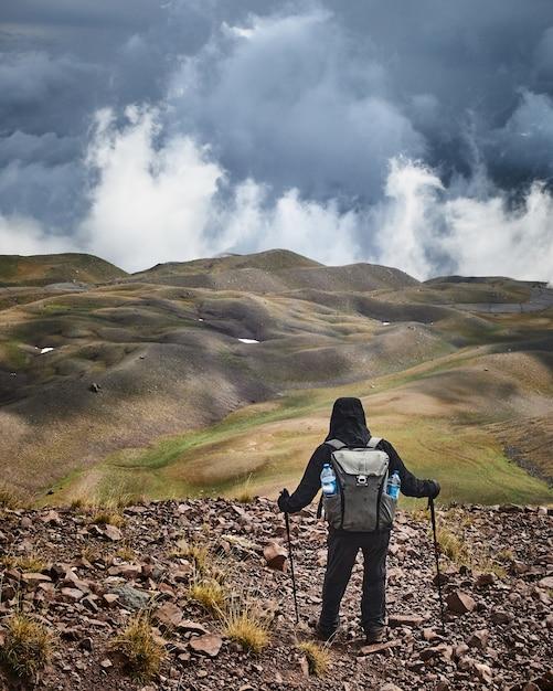 Homem em uma colina apreciando a vista e o céu nublado Foto gratuita