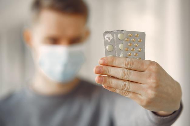 Homem em uma máscara de pé no corredor do hospital Foto gratuita