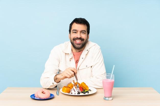 Homem em uma mesa tomando café da manhã waffles e um milk-shake Foto Premium