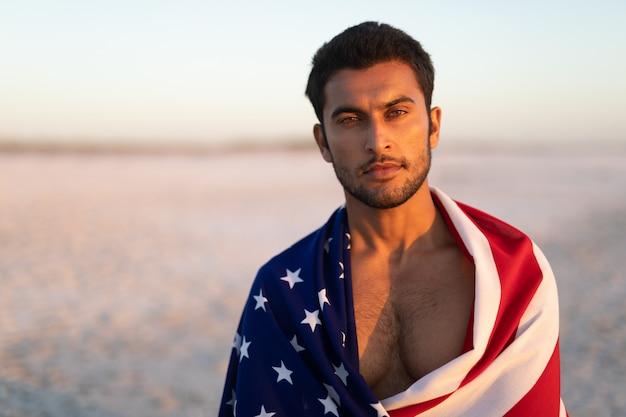 Homem, embrulhado, em, bandeira americana, levantando praia Foto gratuita