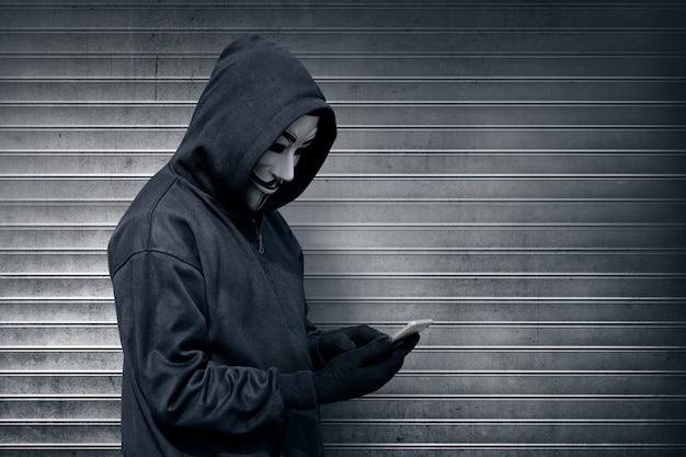 Homem encapuzado com máscara vendetta usando telefone celular Foto Premium