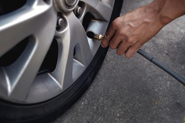 Homem enchendo o ar no pneu. motorista de carro, verificação de pressão de ar e manutenção Foto Premium