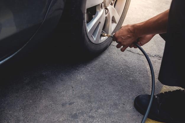 Homem enchendo o ar no pneu. motorista de carro, verificar a pressão do ar e manutenção de seu carro Foto Premium