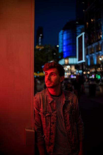 Homem encostado na parede e olhando para longe Foto gratuita