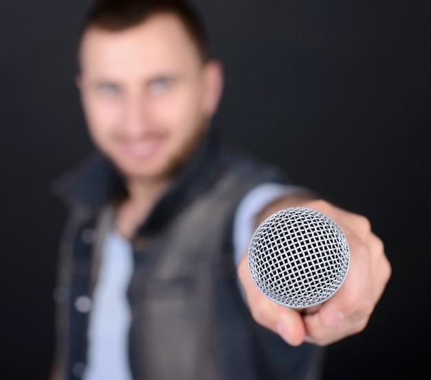 Homem engraçado com microfone cantando karaokê. Foto Premium