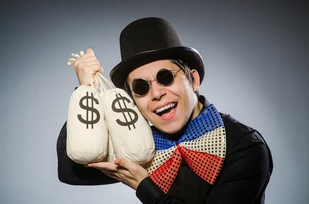 Homem engraçado com sacos de dinheiro dólar Foto Premium