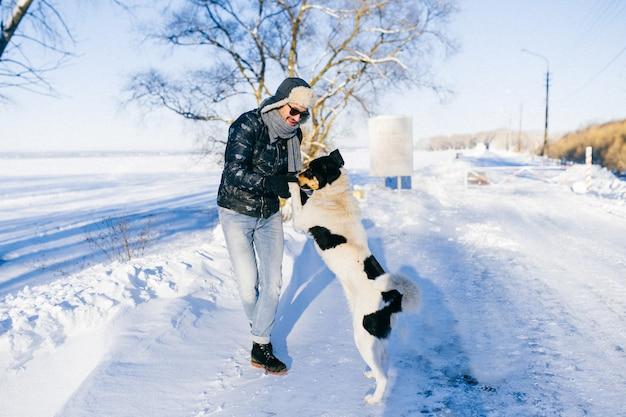 Homem engraçado dançando com cachorro em dia frio de inverno na natureza. Foto Premium