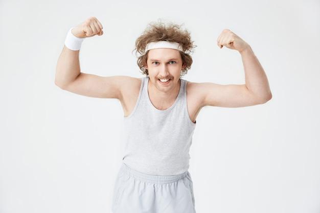 Homem engraçado demonstra bíceps, mostrando os dentes Foto gratuita