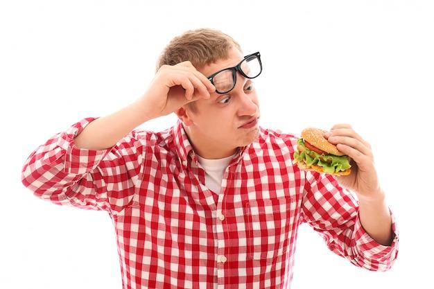 Homem engraçado em copos comendo hambúrguer isolado no branco Foto gratuita
