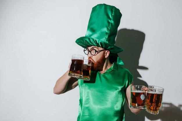 Homem engraçado no traje de st.patriks, bebendo cerveja de dois copos Foto gratuita