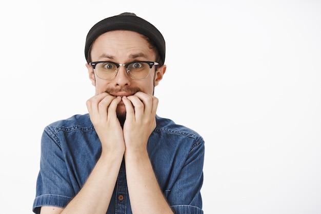 Homem engraçado tímido e inseguro com bigode no gorro preto e óculos roendo as unhas de medo, tremendo e entrando em pânico de medo Foto gratuita