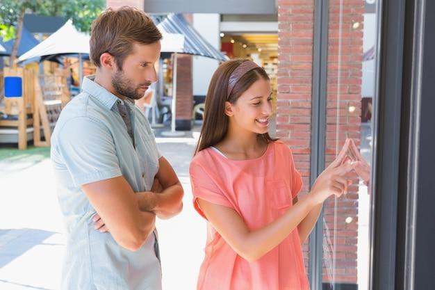 Homem entediado observando sua esposa feliz olhando uma janela Foto Premium