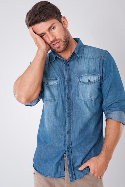 Homem entediado vestindo uma camisa jeans Foto gratuita