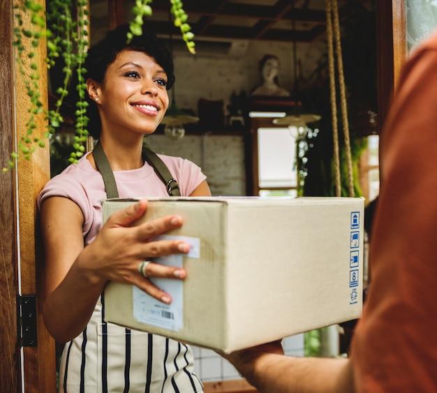 Homem entregar caixa de correio para mulher na frente da parada Foto Premium