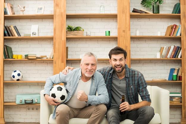 Homem envelhecido com bola e cara jovem com garrafa assistindo tv no sofá Foto gratuita