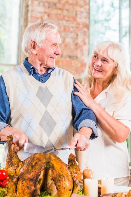 Homem envelhecido corte frango assado na mesa perto de mulher Foto gratuita
