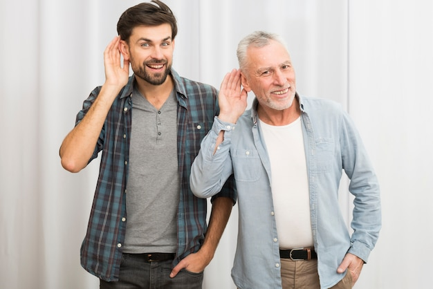 Homem envelhecido e jovem feliz com as mãos perto das orelhas Foto gratuita