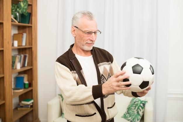 Homem envelhecido, segurando bola, em, sala Foto gratuita