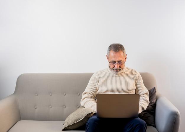 Homem envelhecido, trabalhando em seu laptop com cópia-espaço Foto Premium