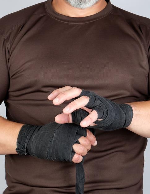 Homem envolve as mãos em bandagem têxtil preto para esportes Foto Premium