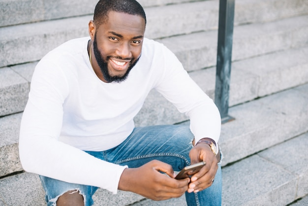 Homem, escada, segurando, smartphone Foto gratuita