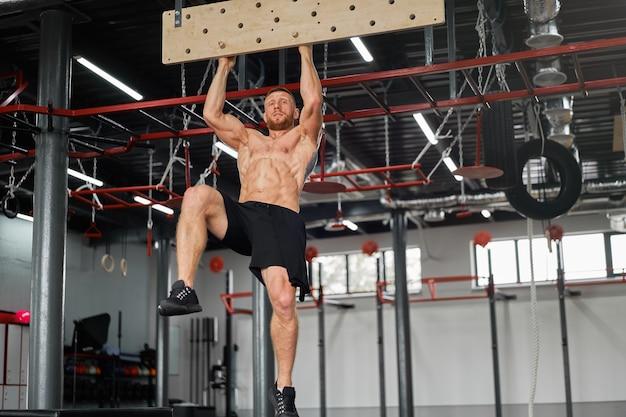 Homem escalando pegboard ginásio atleta treinando força do braço Foto Premium