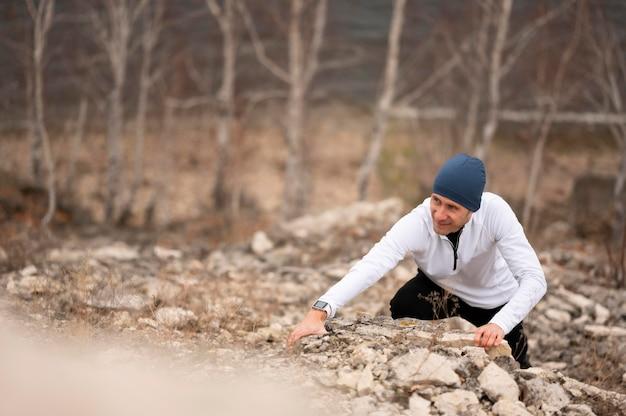 Homem escalando rochas na natureza Foto gratuita