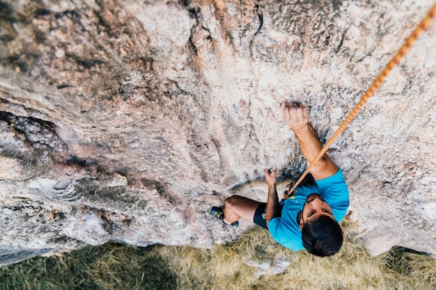 Homem escalando rock com corda Foto gratuita