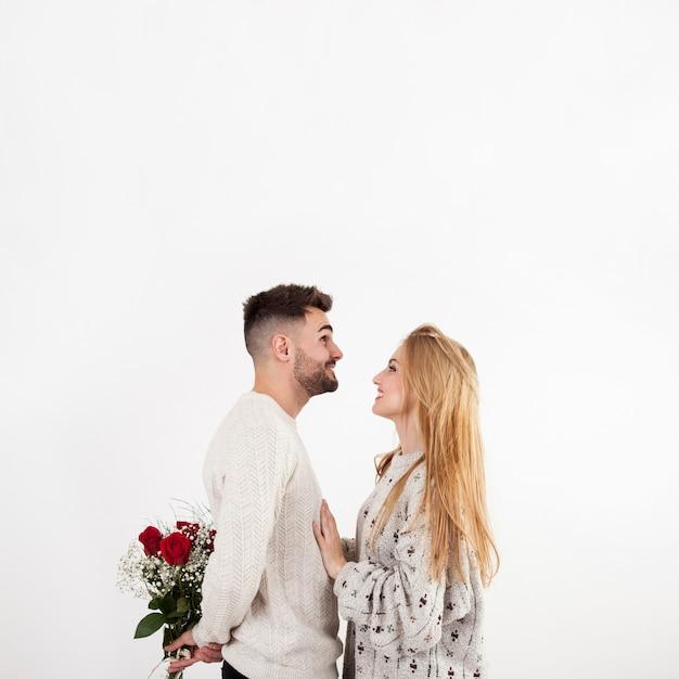 Homem escondendo rosas de mulher Foto gratuita