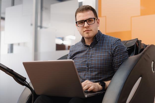 Homem escrevendo código enquanto está sentado na poltrona no escritório Foto gratuita