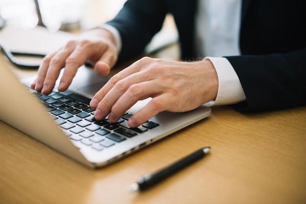 Homem escrevendo no laptop no escritório Foto gratuita