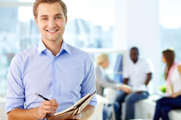 Homem escrita bem sucedida em sua agenda Foto gratuita