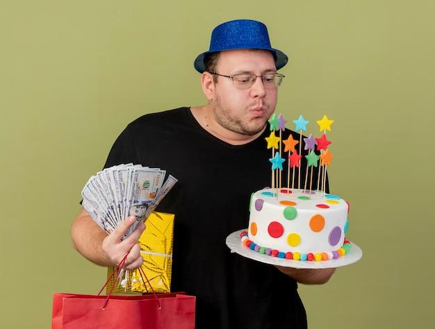 Homem eslavo adulto confiante em óculos óticos, usando um chapéu de festa azul, segura uma sacola de papel de caixa de presente de dinheiro e finge soprar velas em um bolo de aniversário isolado na parede verde oliva Foto gratuita