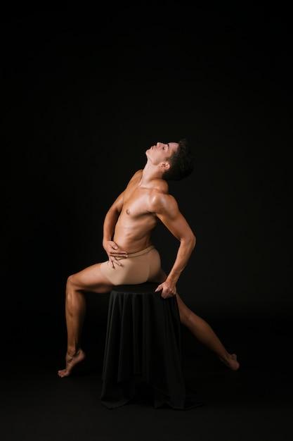 Homem espiritual, estendendo-se pelo corpo sentado na cadeira Foto gratuita
