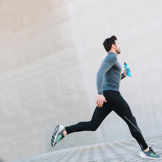 Homem esportivo correndo na rua Foto gratuita