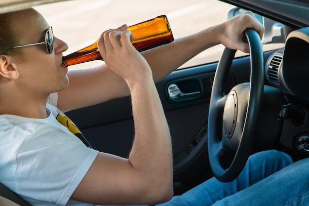 Homem está bebendo cerveja em seu carro Foto Premium