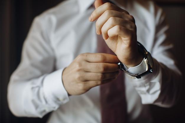 Homem está colocando o relógio no pulso Foto gratuita