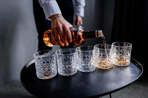 Homem está derramando a bebida de álcool forte no copo Foto gratuita