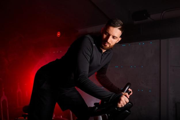 Homem está envolvido em uma bicicleta ergométrica, treinamento pessoal na academia iluminada por néon vermelho, vestindo um agasalho Foto Premium