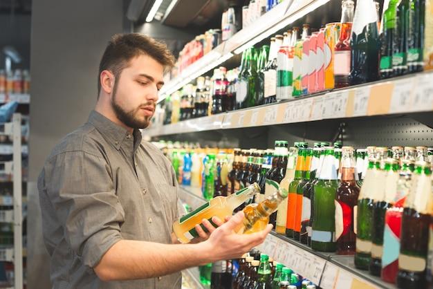 Homem está no setor de bebidas alcoólicas de um supermercado com duas garrafas nas mãos, olha os rótulos e lê Foto Premium