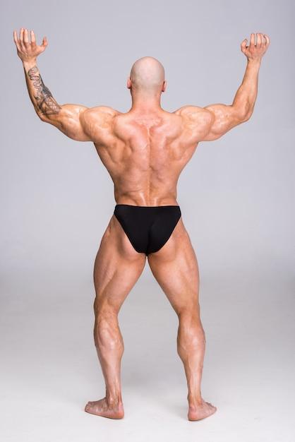 Homem está posando e mostra seus músculos. Foto Premium