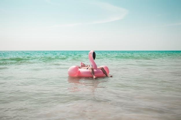 Homem está se divertindo no flutuador de piscina inflável flamingo rosa Foto Premium